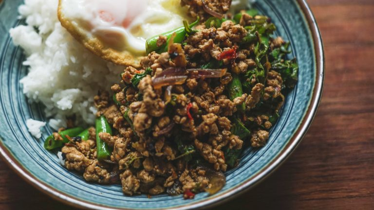 A dish of Pad Krapao Thai Basil Chicken with Jasmine rice and fried egg